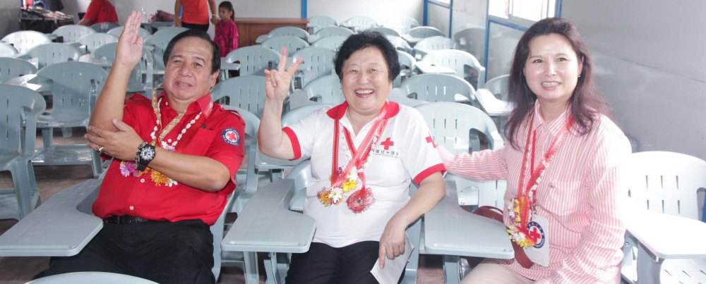 from left: Red Cross (Phil) Chairman and CEO Richard Gordon, Red Cross (China) EVP & Intl Red Cross VP Dr. Baige Zhao and Red Cross (HK) Deputy Chair Mdme Ivy Wu Kwok Sau-ping test out the brand new desk and chairs donated by HK Red Cross at San Jose Central School in Tacloban. Photo taken last February 10, 2014 by Jude Bautista.